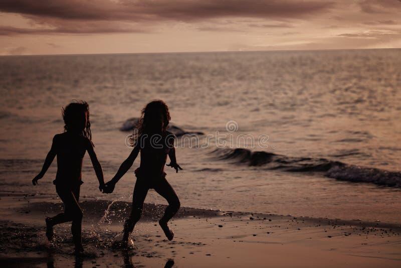 运行年轻人的海滩女孩 免版税库存图片