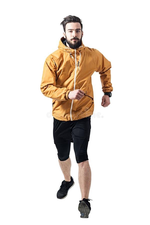 运行往照相机的茶黄夹克的运动员 免版税库存照片