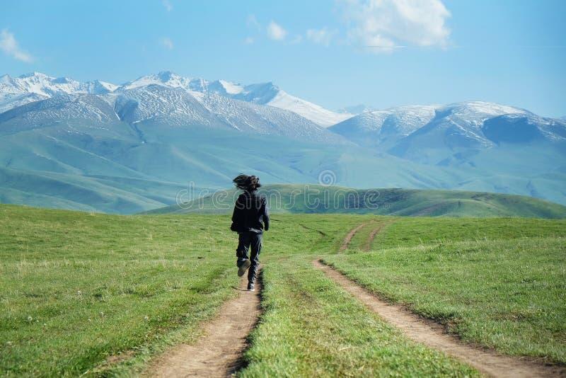 运行沿乡下公路的黑色衣服的一个人往山 库存图片