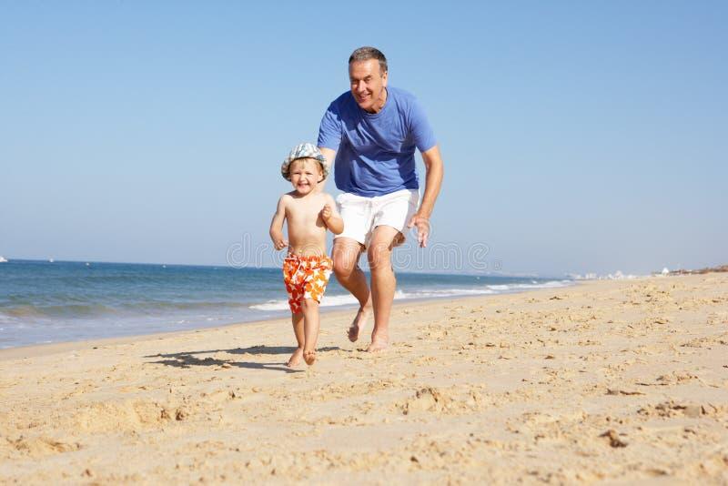 运行沿海滩的祖父和孙子 免版税图库摄影