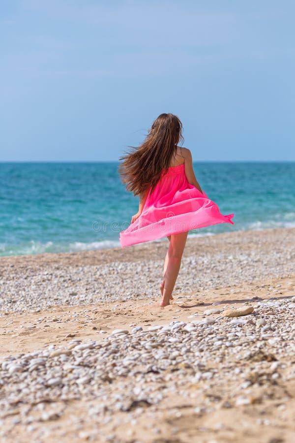 运行沿Pebble海滩的桃红色礼服的女孩 库存图片
