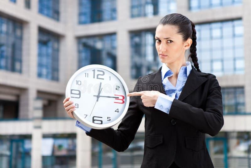 运行的女实业家显示时间 免版税库存图片