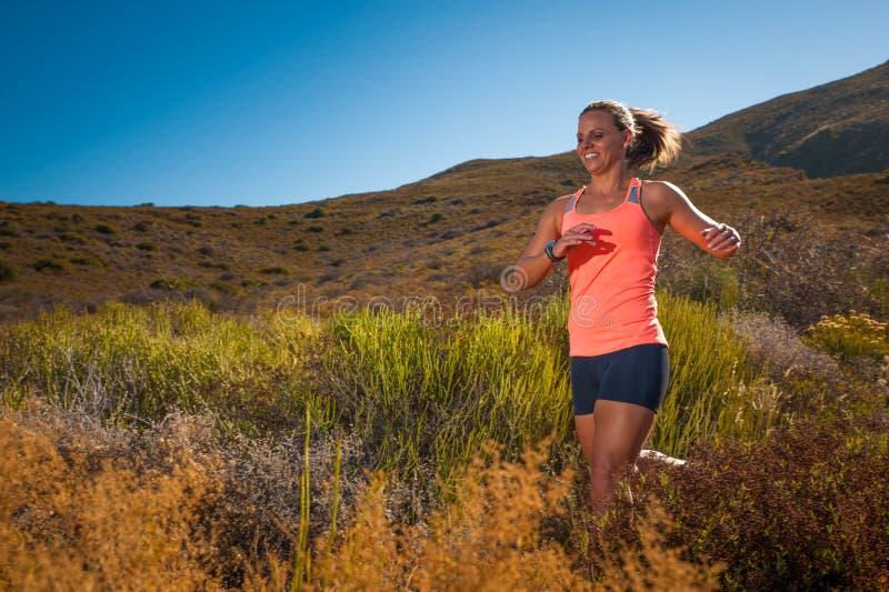 运行通过山风景的白肤金发的母足迹赛跑者 库存图片