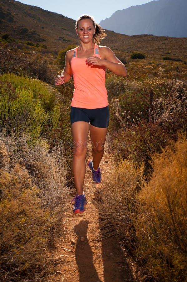 运行通过山风景的白肤金发的母足迹赛跑者 库存照片