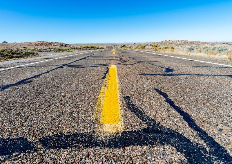 运行通过沙漠的一条不尽的直路的看法 免版税库存图片
