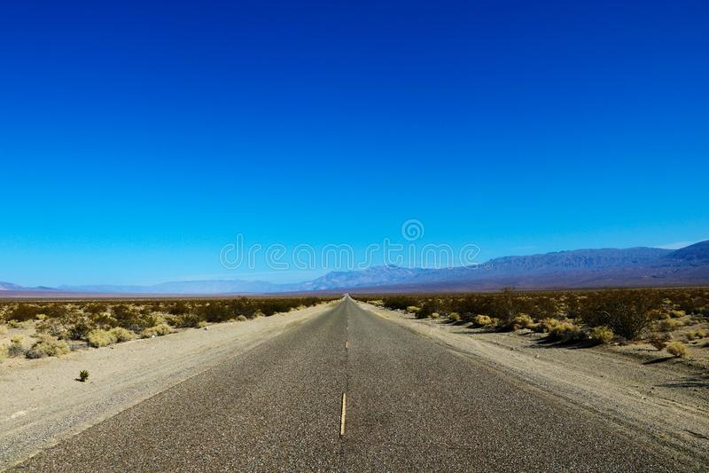 运行通过美国西南的贫瘠风景的一条不尽的直路的经典全景视图以极端热 库存图片