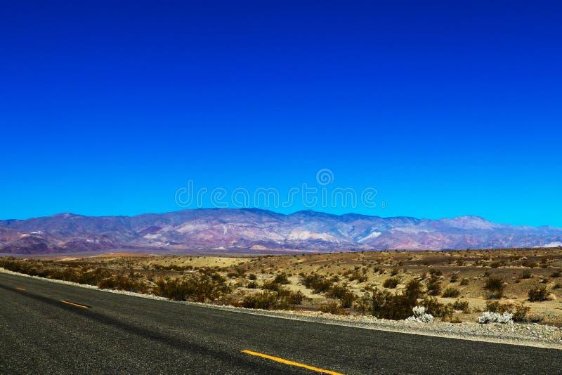 运行通过美国西南的贫瘠风景的一条不尽的直路的经典垂直的全景视图与 库存照片