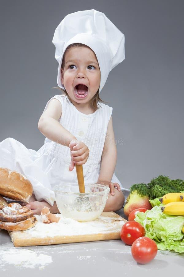运转与的厨师制服的白种人小女孩扫和厨房玻璃器皿 免版税库存图片