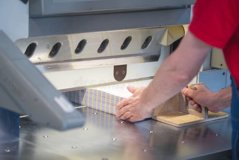运转在切削刀断头台机器的工作者的手在打印工厂 免版税库存照片