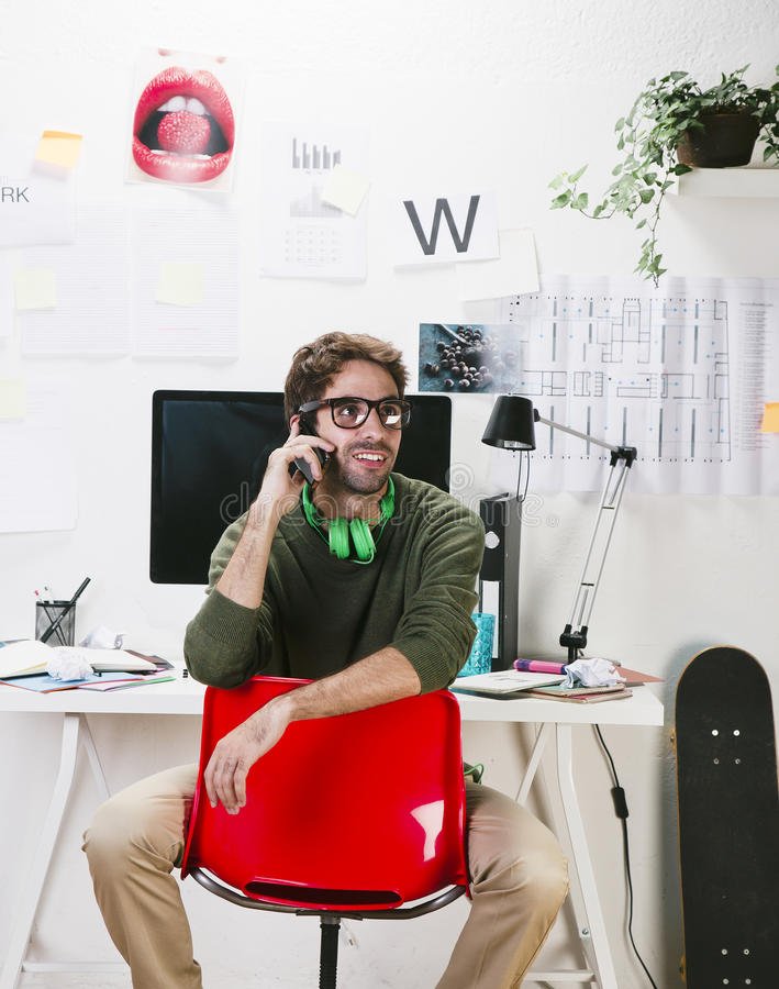 运转在办公室的电话的年轻创造性的设计师人。 免版税库存图片
