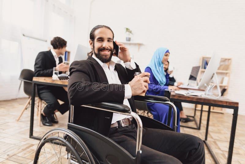 运转在办公室的轮椅的残疾阿拉伯人 人在电话和饮用的咖啡谈话 库存图片