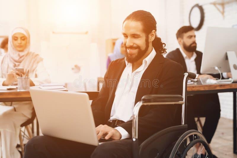 运转在办公室的轮椅的残疾阿拉伯人 人研究膝上型计算机 免版税库存照片