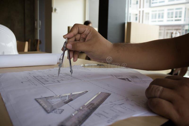 运转在图纸,建筑概念的工程师的手 eng. 免版税库存图片