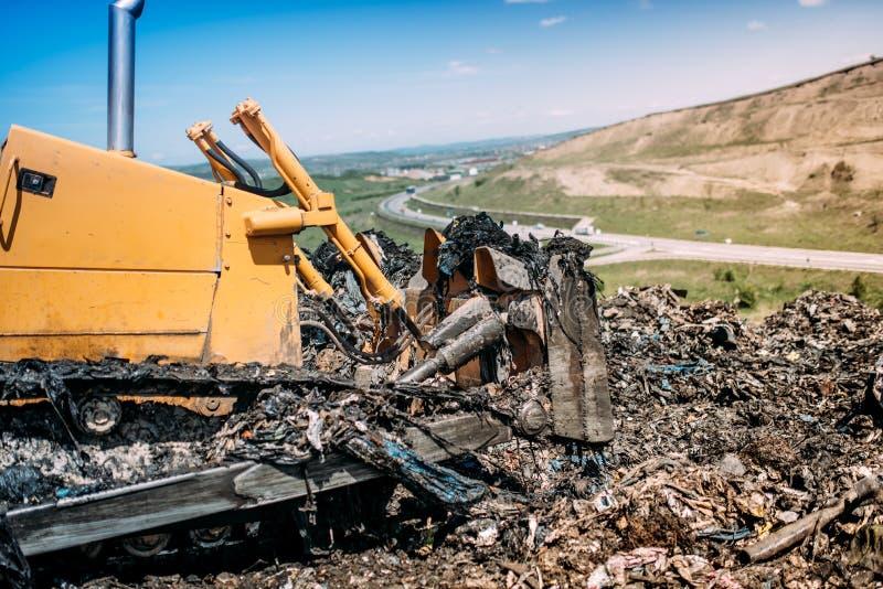 运转在垃圾倾弃场的工业推土机 免版税库存图片