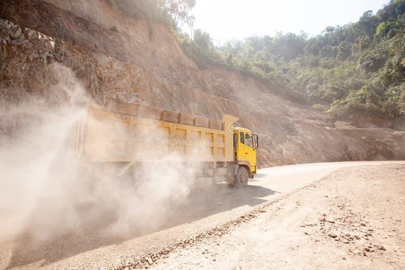 运转在多灰尘的山路在工地工作,在老挝越南边界附近的一条新的修路的黄色翻斗车 免版税库存图片