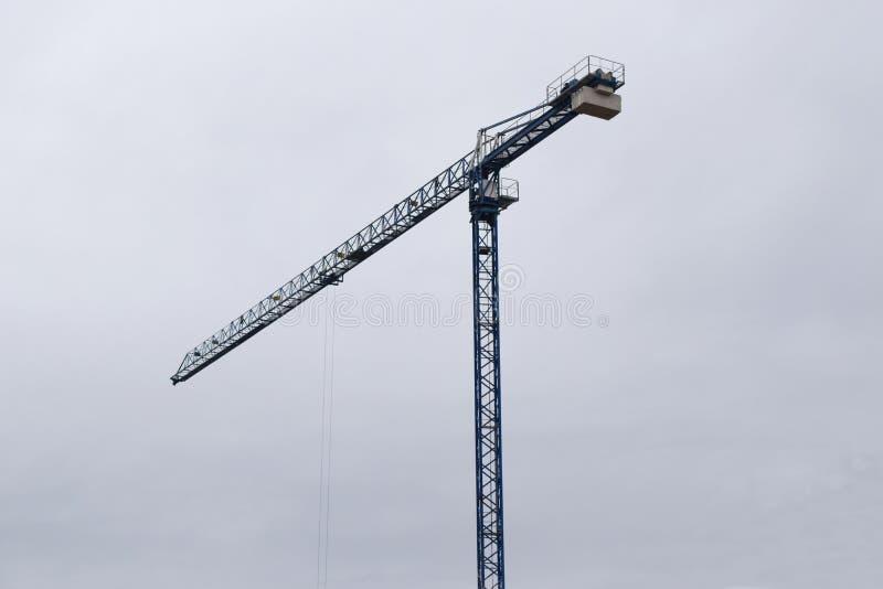 运转在工地工作的蓝色起重机在多云天空下 免版税库存照片