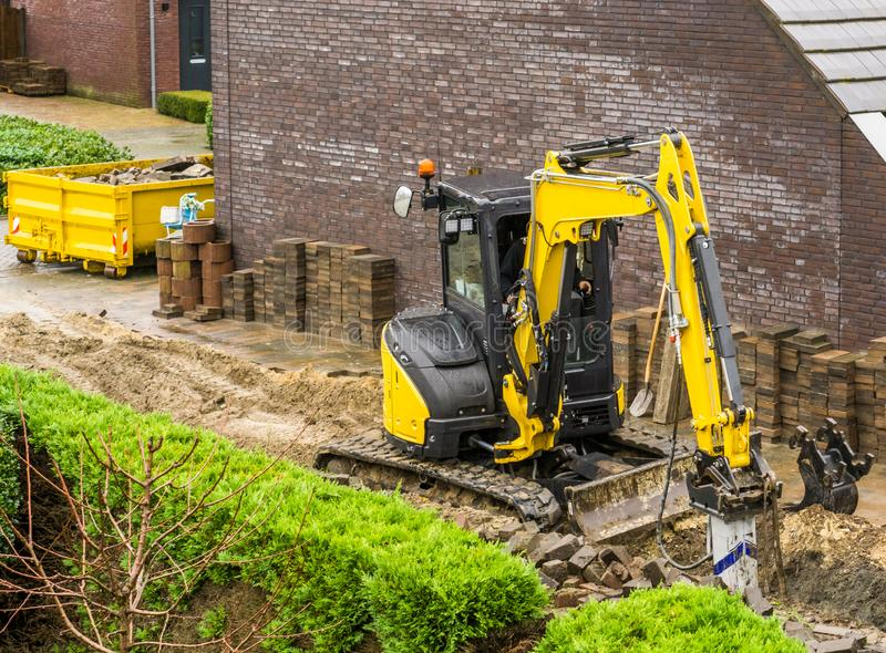 运转在庭院建筑的挖掘机的机器在一个现代邻里 库存图片
