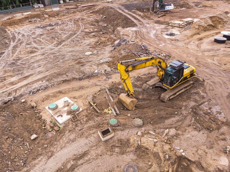 运转在建造场所的黄色挖掘机 鸟瞰图 免版税库存照片