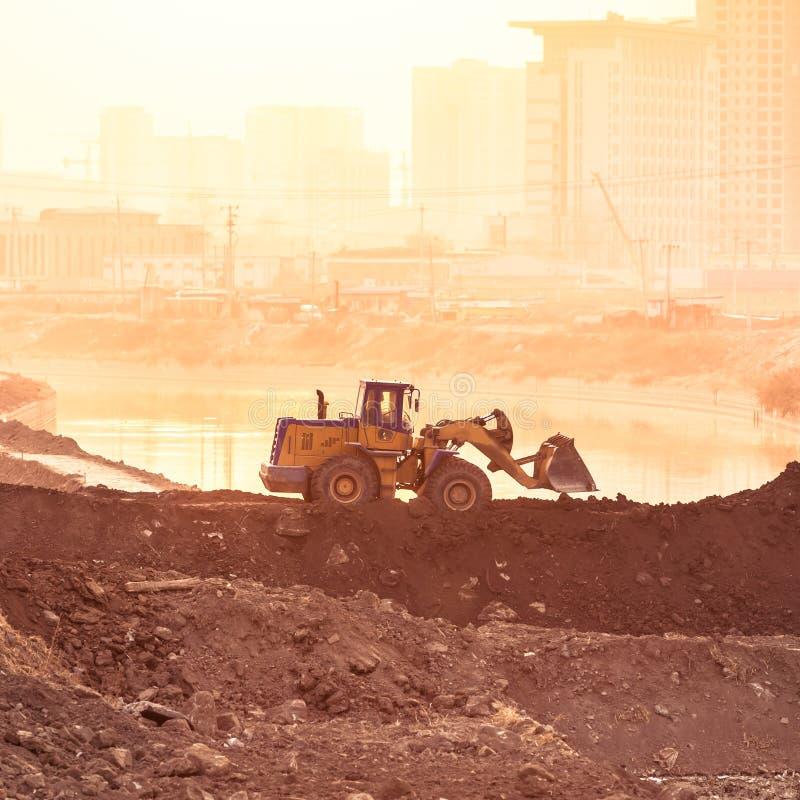 运转在日落的重的轮子挖掘机机器 免版税库存图片