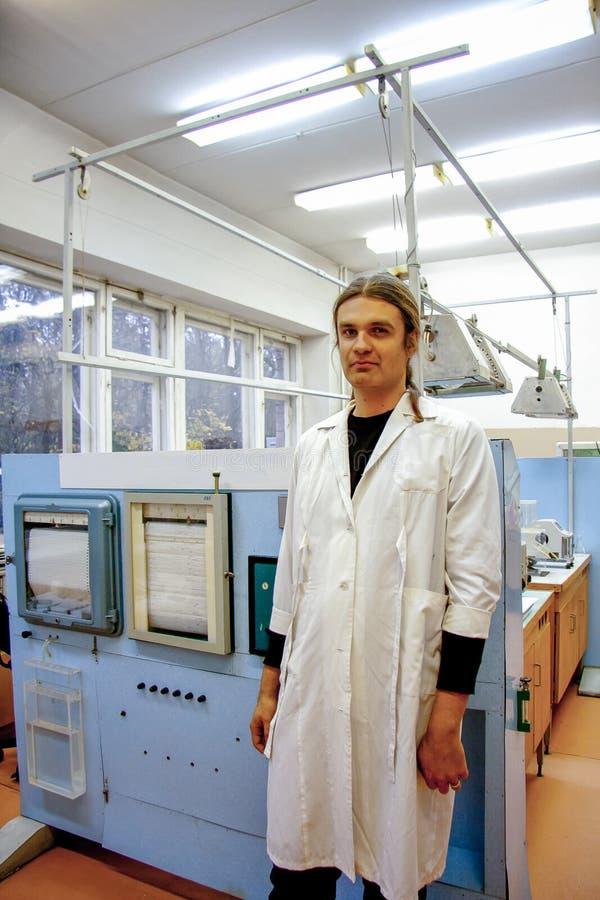 运转在植物生理实验室的白色长袍的男性科学家  免版税库存照片