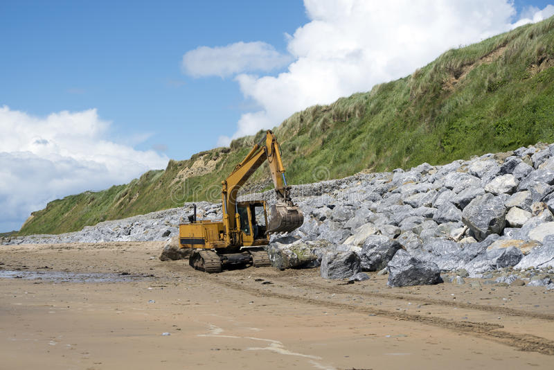 运转在沿海保护的机械挖掘机 库存照片