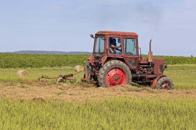 运转在领域的老拖拉机 免版税库存图片
