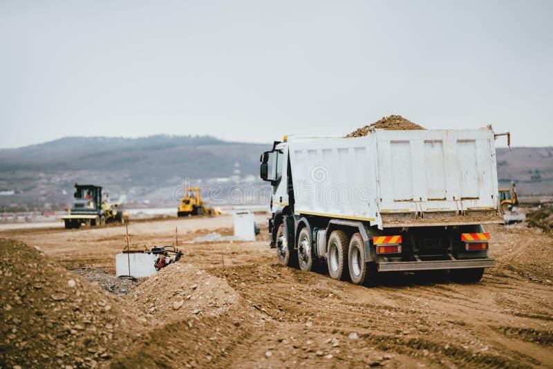 运转在高速公路建造场所,装货和卸载地球的工业倾销者卡车 耐用机械活动 库存照片