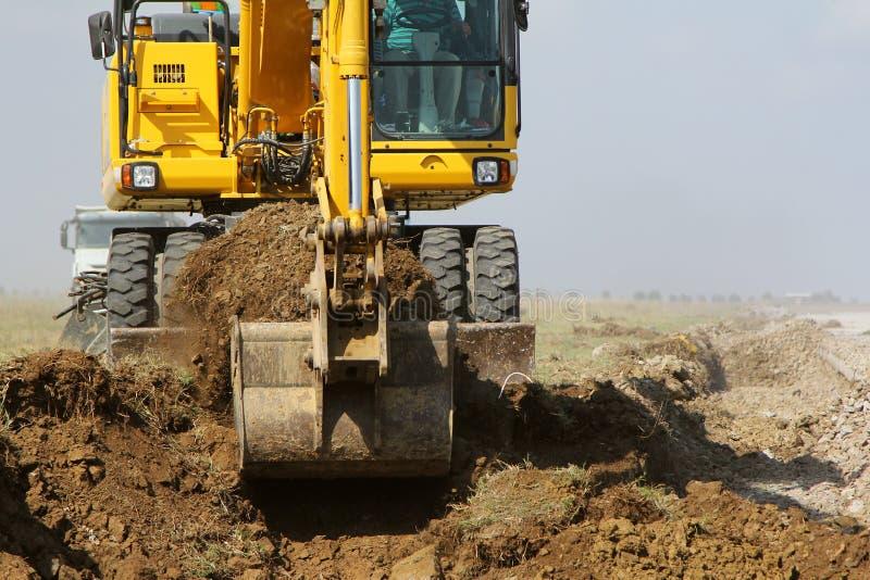 运转在高速公路建造场所的履带牵引装置挖掘机 库存照片