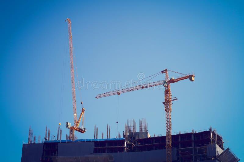 运转在建造场所建筑业的机械起重机 库存照片