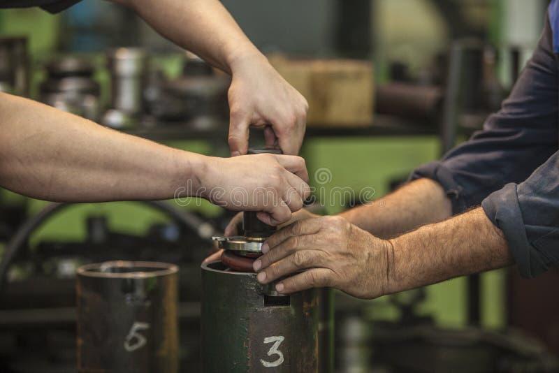 运转旋转的男性手在一家老工厂分开安装 图库摄影