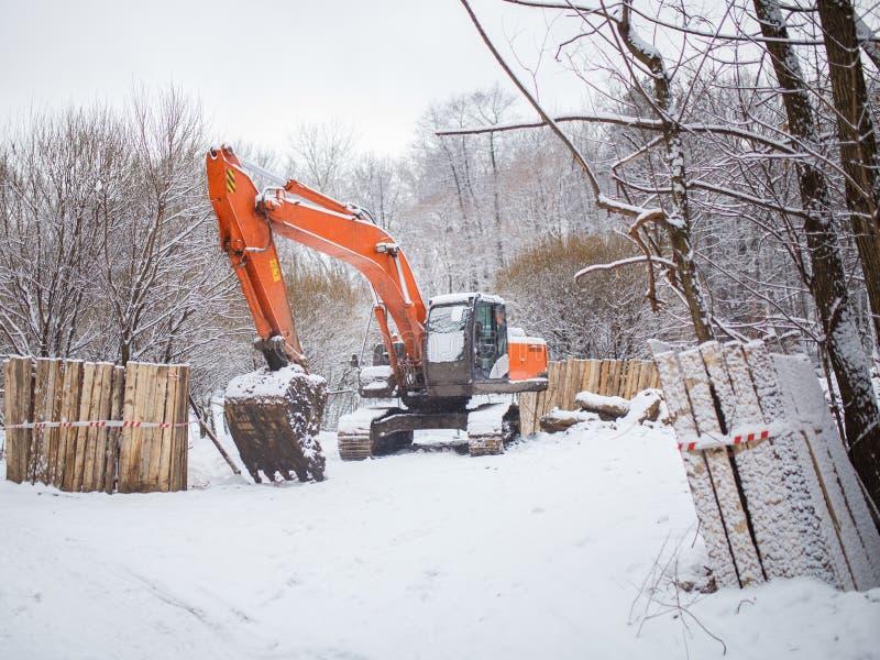 运转的挖掘机照片在冬日 免版税库存照片