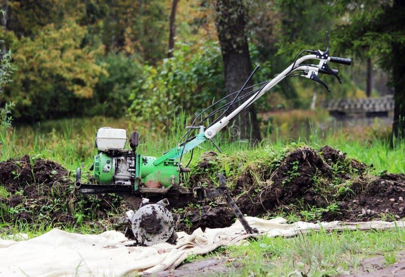 运转的马达耕地机翻土机在Gatchina公园在地面等待的工作 免版税库存图片