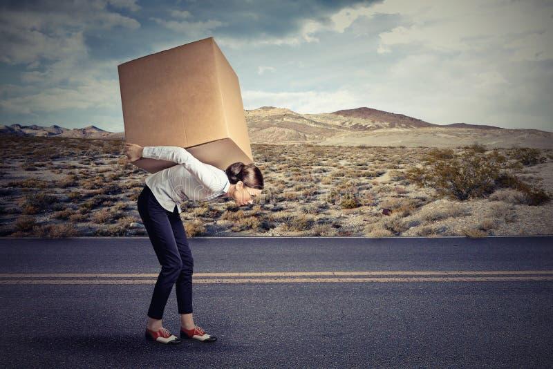 运载一个大箱子的妇女 免版税库存图片