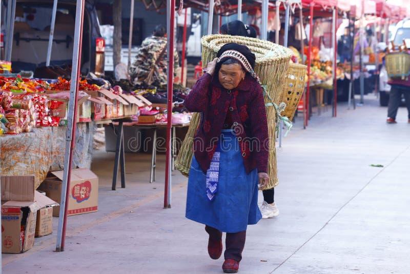 运载一个大篮子的一名年长妇女在沙溪市场上在云南,中国 库存图片