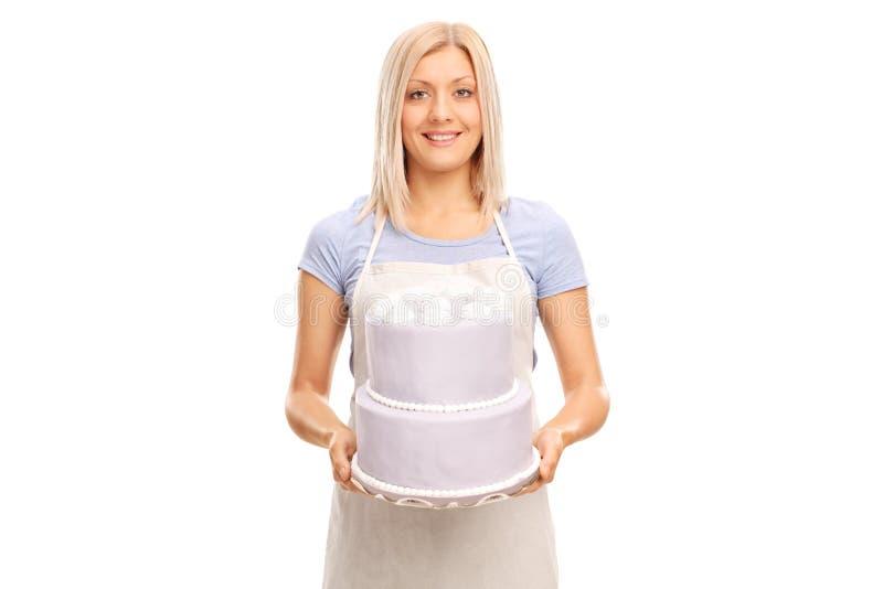 运载一个大蛋糕的女性点心师 免版税库存照片