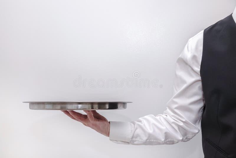 运载一个空的银色盘子的侍者/男管家 免版税图库摄影