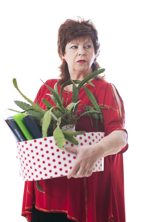 运载一个箱子个人项目的被解雇的妇女 免版税库存图片