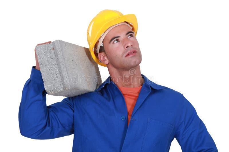 民工运载的cinderblock 免版税库存照片