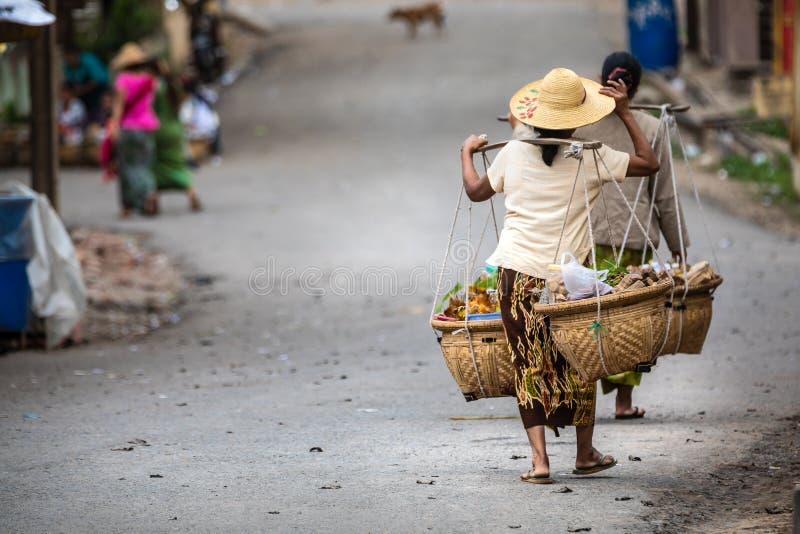 运载与一个典型的方法的食物的缅甸妇女 免版税库存照片
