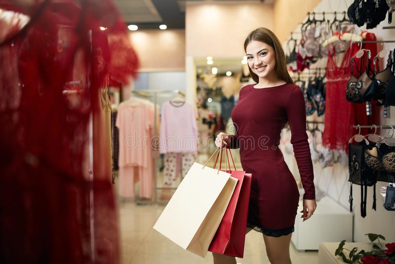 运载与女用贴身内衣裤的微笑的妇女一些购物袋在背景存放陈列室 相当微笑的白种人女孩 图库摄影