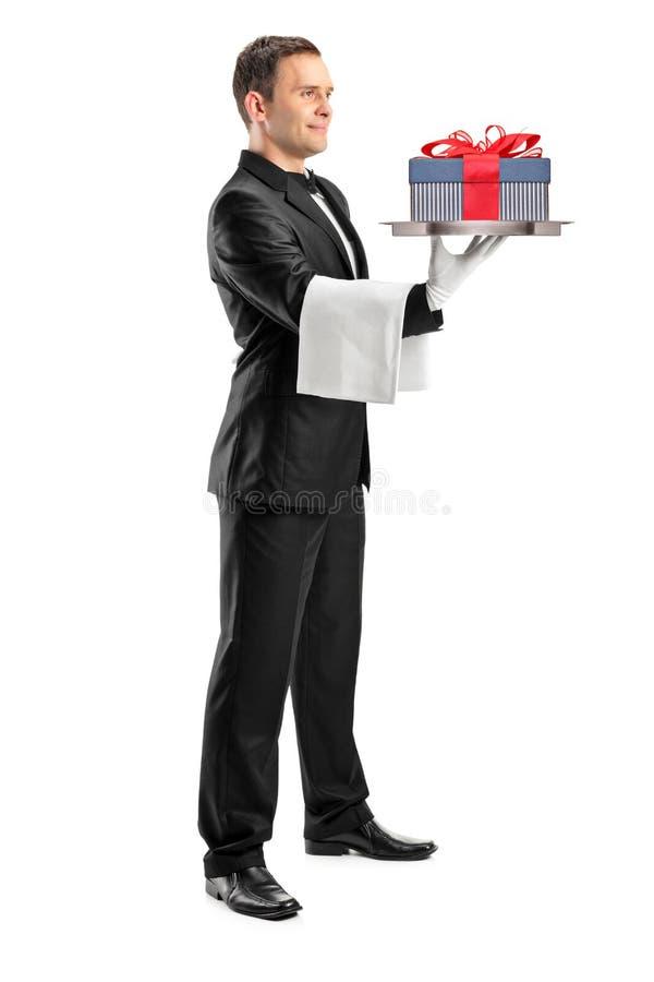 运载与礼品的男管家一个盘对此 免版税图库摄影