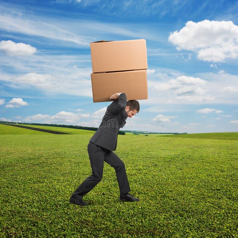 运载两个重的箱子的人在室外 免版税库存图片
