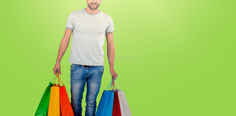运载五颜六色的购物袋的年轻人画象的综合图象反对白色背景 库存图片
