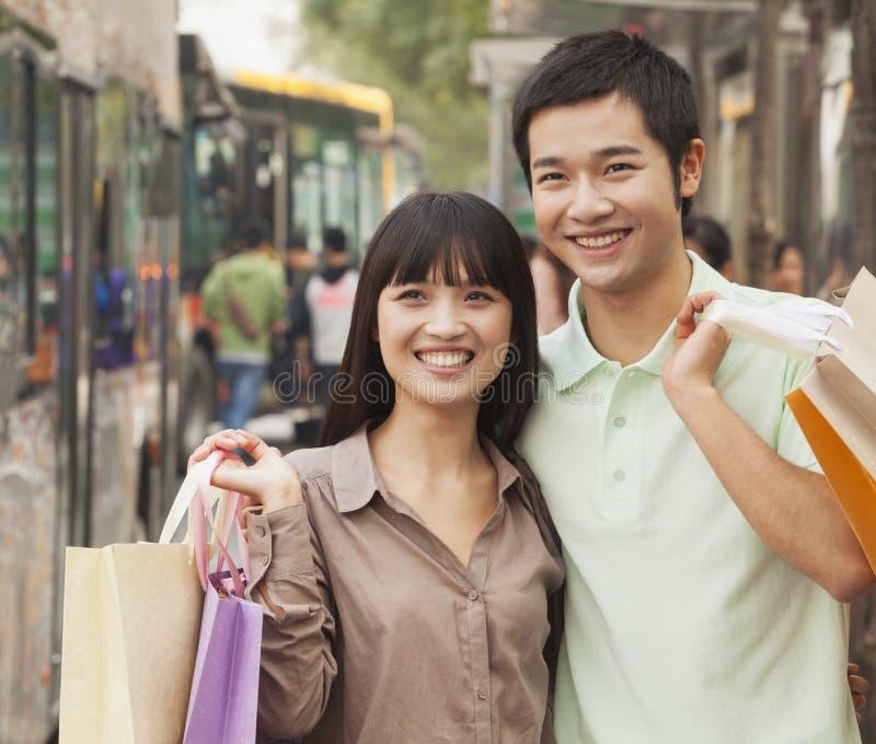 运载五颜六色的购物袋和等待公共汽车的微笑的年轻夫妇画象在公共汽车站,北京,中国 免版税图库摄影
