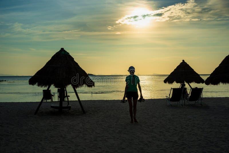 运载他们的在日落海滩的妇女剪影鞋子 免版税库存照片