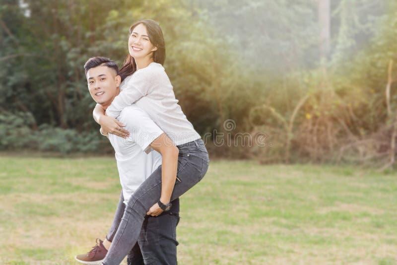运载他的女朋友的男朋友扛在肩上 免版税库存图片
