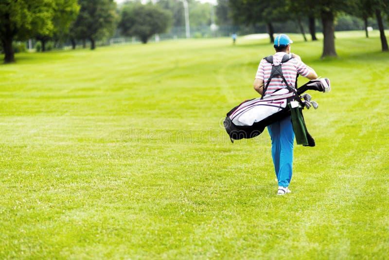 运载他的设备的高尔夫球运动员 库存图片