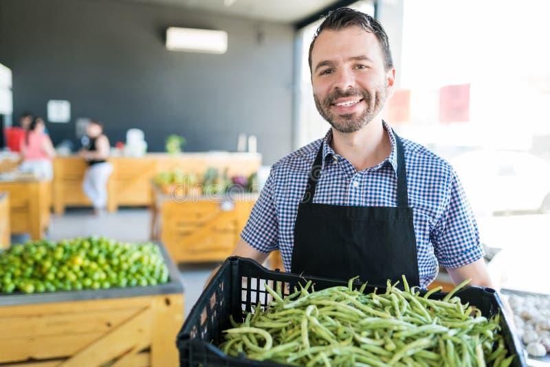 运载健康菜的男性工作者在商店 库存图片
