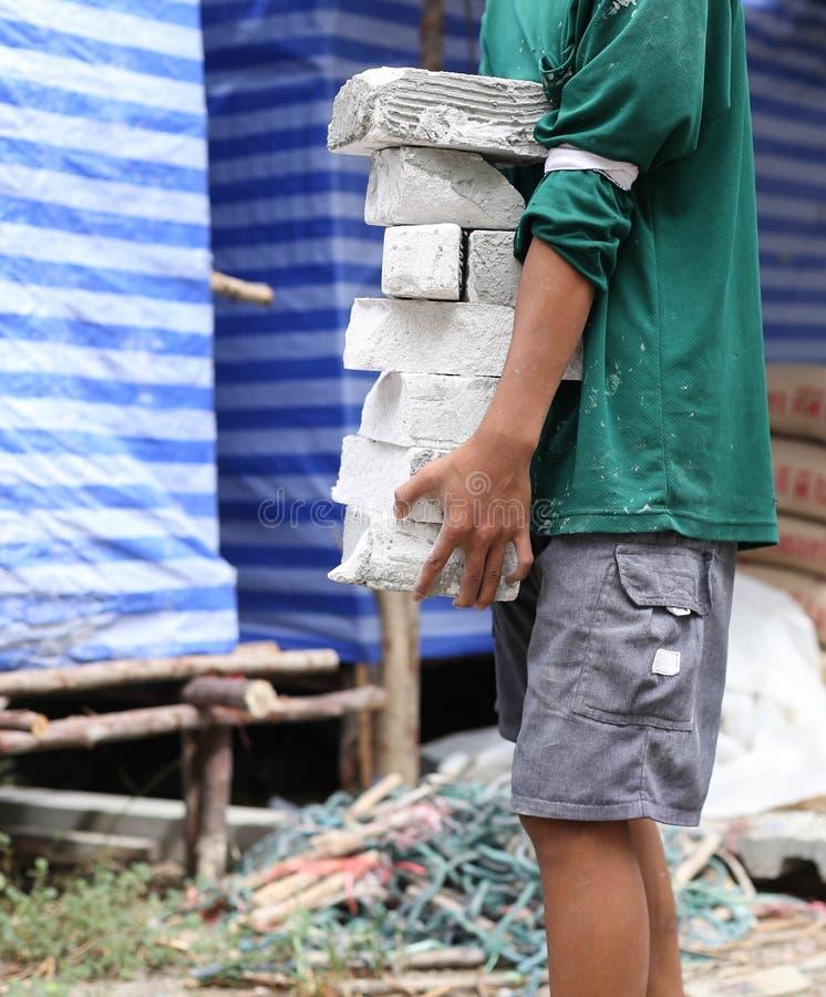 运载具体块的建筑工人 免版税库存图片