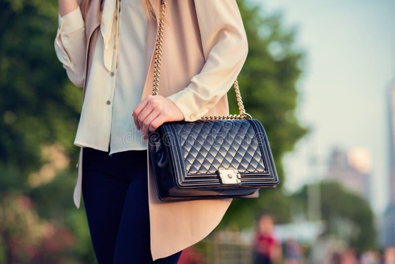 运载典雅的钱包的妇女在城市公园请求 免版税图库摄影